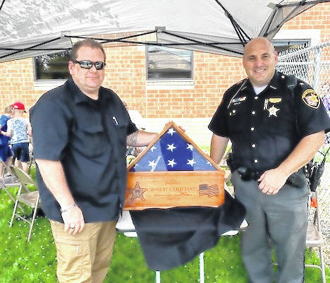 Courtesy Photo Morrow County Sheriff's Office Detective Rob Chalfant retired June 30. He has served 30 years as a Deputy Sheriff, 25 of those years at the Morrow County Sheriff's Office. The flag pictured in the case is the flag that was flying at the Sheriff's Office on his final day on the job. Shown with Chalfant is Sheriff John Hinton.