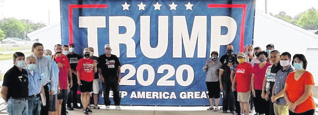 MAGA attendees surrounding a giant President Donald Trump banner, which will hang in the Morrow County Republican's headquarters.