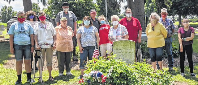 At the Grave of Rev. George Gordon at Iberia Cemetery are Morrow County Genealogical Society members. From left in back: Janet Rhodebeck, Dan Rhodebeck, Fred Miller, Janet Miller, Russ Mayer, and Dave Ufferman. In front from left: Laura Artrip, Becky Kunze, Judy Mayer, Ann Artrip, Phylis Miller, Donna Ufferman and Emma Artrip.