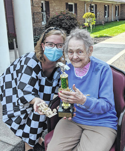 """Woodside employee Bailey Huston, at left, celebrates the Best of Show winner's trophy with a resident. They worked on the winning, """"Bulldog"""" race care for two weeks. Bailey really got into the racing spirit with her checkered top."""