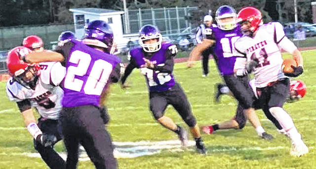 Cardington wide receiver Trey Brininger picks up yardage in the first quarter Friday night. Pursuing are Mount Gilead's Andy Williamson, Chuy Rubio and Devon Hill.