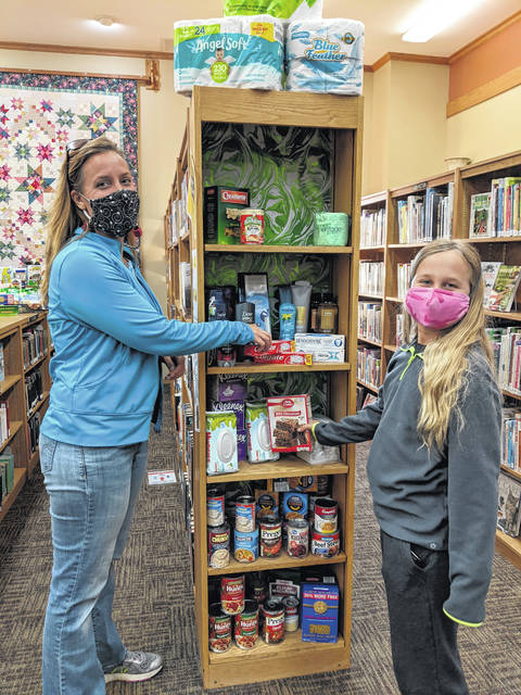 Jennifer Trainer and her daughter Kayla add donations to Selover Library's Helping Hands Drive.