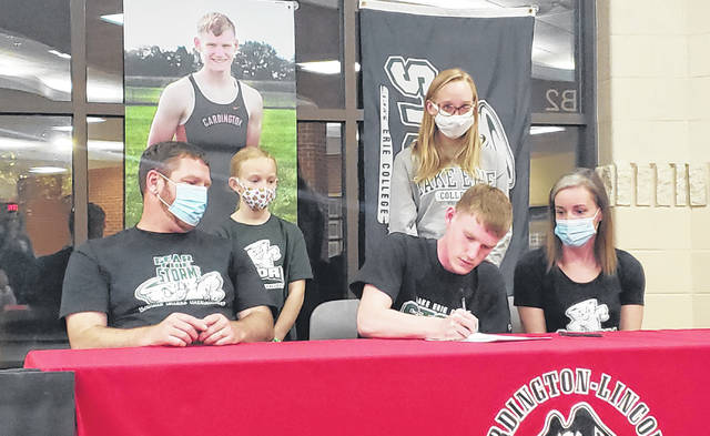 Cardington senior Mason White signs his letter of intent to run cross country and both indoor and outdoor track for Lake Erie College. With him are, back row (l-r): sisters Mickenzie and Morgan White. Front row: parents Travis and Tabitha White.