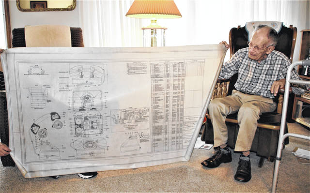 Russell Badgley of Galion celebrated his 100th birthday on Nov. 25. He is shown holding a schematic of a telephone that he drew freehand while he was an employee of North Electric.