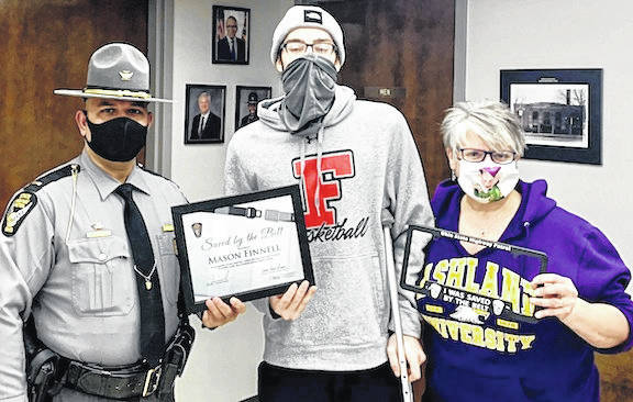 Courtesy Photo Fredericktown resident Mason Finnell receives the Saved by the Belt certificate presented by Ohio State Highway Patrol Lieutenant Grewal, Mount Gilead Post commander. His mother Tara is at right.
