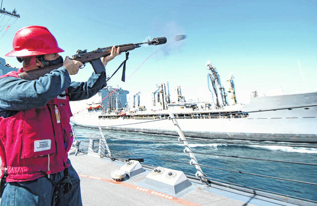 NORTH ARABIAN SEA — Gunner's Mate 3rd Class Gage Duncan, from Cardington, fires a shot line from the deck of the guided-missile destroyer USS Sterett (DDG 104) to the fleet replenishment oiler USNS Leroy Grumman (T-AO 195) during a replenishment-at-sea Jan. 26. Sterett is part of the Nimitz Carrier Strike Group and is deployed to the U.S. 5th Fleet area of operations to ensure maritime stability and security in the Central Region, connecting the Mediterranean and Pacific through the Western Indian Ocean and three critical chokepoints to the free flow of global commerce.