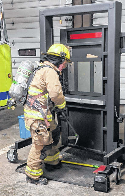 An academy student hammers on the on the Forcible Entry Simulator as part of the certification exam. The door simulates forcible entry into a burning building.