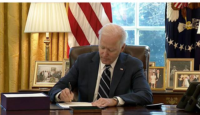 President Joe Biden signs the American Rescue Plan package of legislation March 11, 2021, at in the Oval Office at the White House.