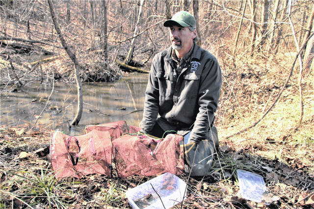 Crawford Park District Director Josh Dyer collects live animal traps from a vernal pool at the new Sandusky Headwaters Preserve in Leesville. Development of the 38-acre preserve located along Ohio 598 across from Lowe-Volk Park is being funded by a grant the Ohio Department of Natural Resources H2Ohio initiative.