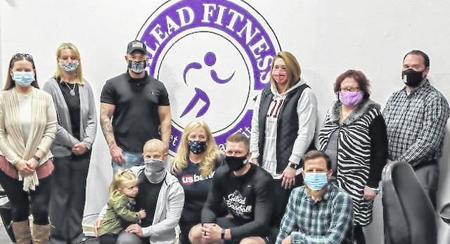 From left at Gilead Fitness grand re-opening ribbon cutting: Amanda Welch, Kim Bood, Brandon Fleming, Amanda Bush, Jeanine Girard and Mount Gilead Mayor Jamie Brucker. Kneeling are Eugene Ambler, Erin Kelty, Greg Gompf and Morrow County Chamber of Commerce Director Joel Smythe.