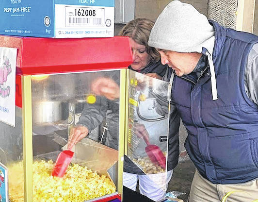 United Way Executive Director Jodi Hayes and Board President Sheriff John Hinton make popcorn Thursday morning during the sixth annual Radiothon.