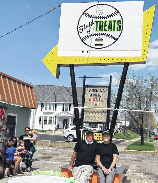 Field of Treats owners Belisa and Tim Sherman by their new sign. In the background are Mechelle Dodrill and Kaci Lanker, with their children, who enjoyed an ice cream cone.
