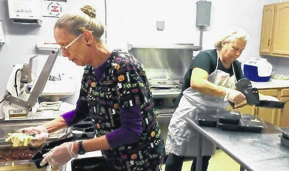 Volunteers at Seniors on Center prepare meals for delivery last November.