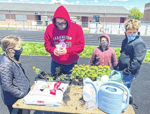 Luke Goers, a senior FFA member, teaches third grade students how to plant flowers during Food for America Day.