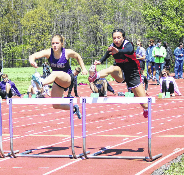 Mount Gilead's Adriana Tinch (l) and Cardington's Bella Scurlock battle for position in the 100-meter hurdles on Saturday.