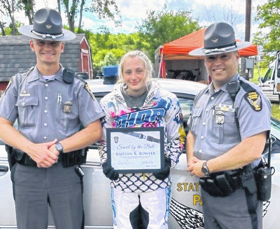 """Trooper E. M. Reidenbach (left) and Sergeant B. D. Brown (right) are shown with Bernice Cline and Kaitlyn Bowyer receiving """"Saved by the Belt"""" certificates."""