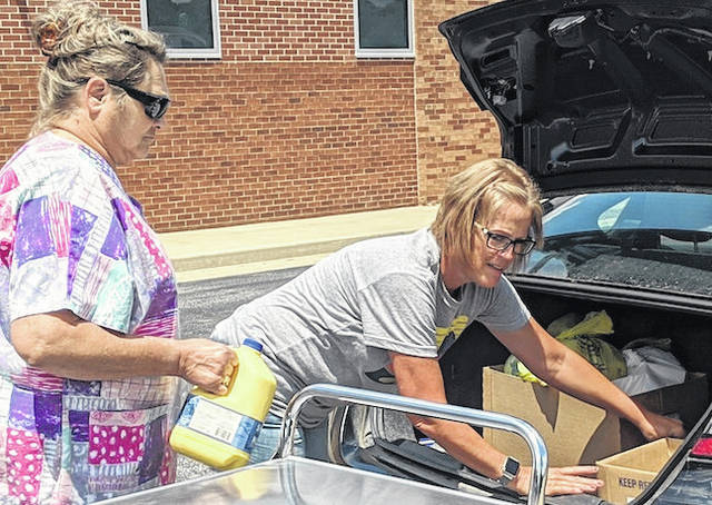 Cafeteria workers Robin LaRoche and Bonnie Bostic load meals and milk for a family behind Mount Gilead High School.