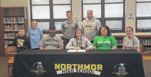 Northmor's Julia Kanagy signs to run cross country for Mount Vernon Nazarene University. Pictured with her are (l-r) siblings Nicholas and Veronica, father Kyle, MVNU coach Simon Taylor, Kanagy, Northmor coach Mark Yaussy, mother Heather and sister Hannah.