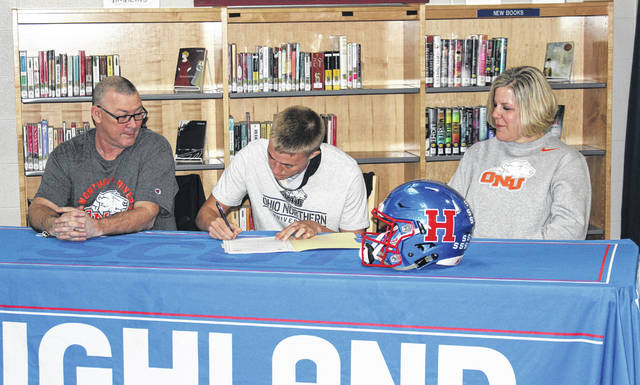 Landon Remmert of Highland signs to attend Ohio Northern University, where he will compete in both football and track and field. Sitting with him are his parents, Lincoln and Tiffany.