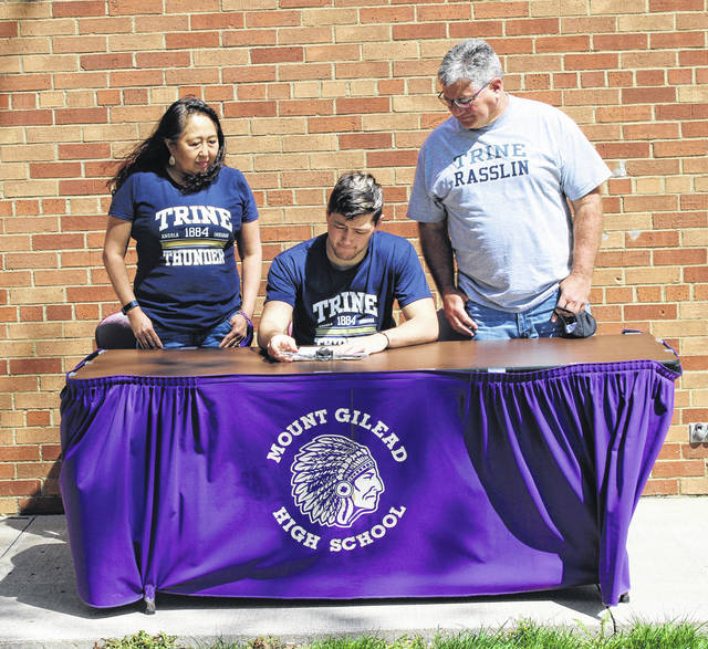 Mount Gilead's Andy Williamson signs his letter of intent to compete on the wrestling team at Trine University. With him are his parents, Susan and Mike.