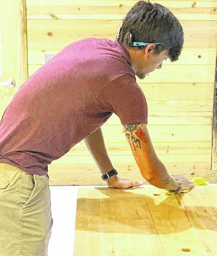 Joshua Wallace cleans a table at Flying Horse Farms July 7.