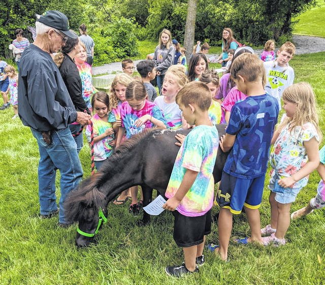 Jack Walker shows a miniature horse to children at Selover Library's Tails and Tales on the Trail event at Highland Community Park.