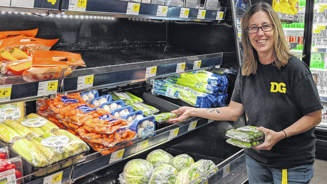 Marengo Dollar General Manager Linda McCurdy stocks some cucumbers in the fresh produce aisle after a truck delivered on Monday morning. The store receives three deliveries of fresh produce every week.