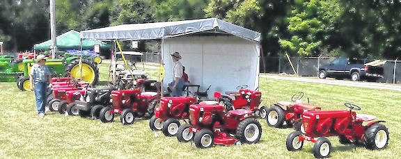 Display at Farm Days of bright red restored vintage Wheel Horse garden tractors at the recent Farm Days event. The display of Wheel Horses owned by Larry Eads and Keith Jones included one military-colored vehicle.