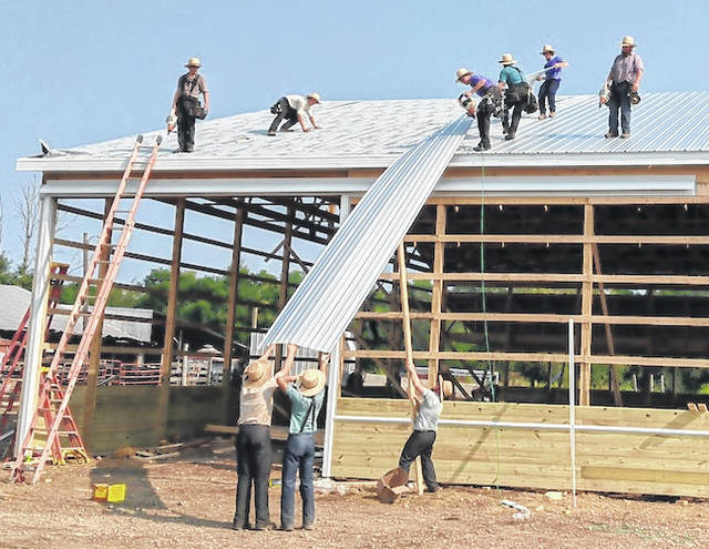 Some of the 40 Amish men who worked at the barn raising finish the sheet metal roof on the 90-foot by 120-foot barn.