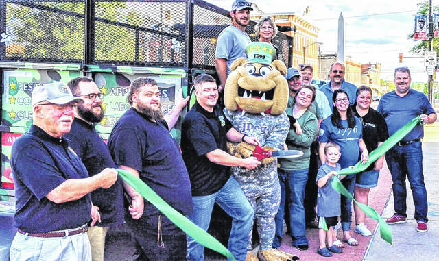 JDog Junk Removal and Hauling at the Chamber of Commerce ribbon cutting for their business. Casey Shenefield holds the scissors, while his partner Billy Davis wears the JDog mascot garb.