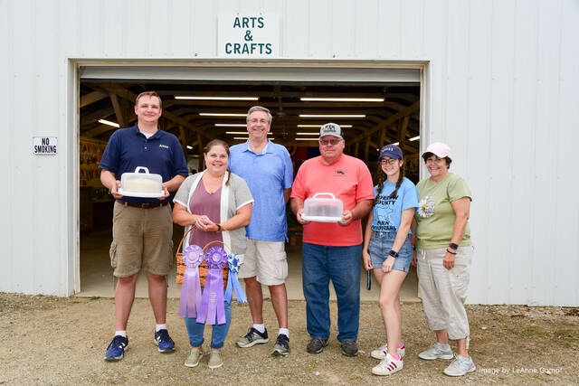 From left: Andrew Wick and Don Wick with the reserve champion cake baked by Michelle Ferraraccio, center, in memory of her sister, Pam Frazier it was purchased by the Wicks for $375. On the right are the purchaser of the grand champion cake, also baked by Melissa. It is being held by Tom Blankenship of the Morrow County Pork Producers who purchased it for $400. On the far right are are Cassidy and and Mary Neviska with the Pork Producers.
