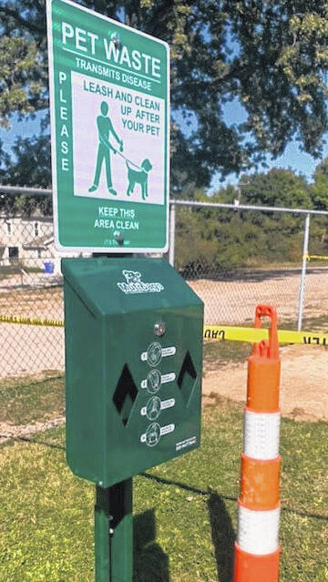 Dog park includes benches and a trash bag dispenser for humans to clean up after their furry friends.