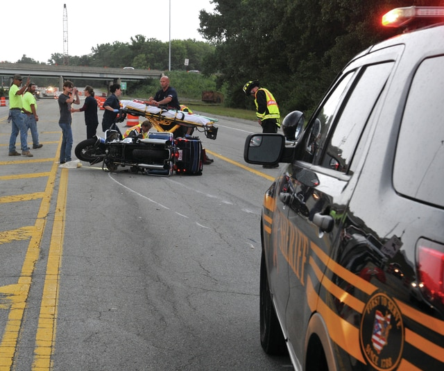 Mike Ullery | Daily Call Paramedics from the Piqua Fire Department prepare to transport the victim of a Friday evening motorcycle crash on Co. Rd. 25A.