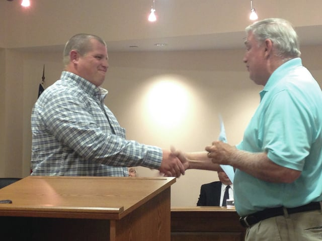 TJ Mullens (left) shakes hands with village of Covington Mayor Ed McCord (right) after Mullens is sworn in as a new, full-time police officer for Covington.