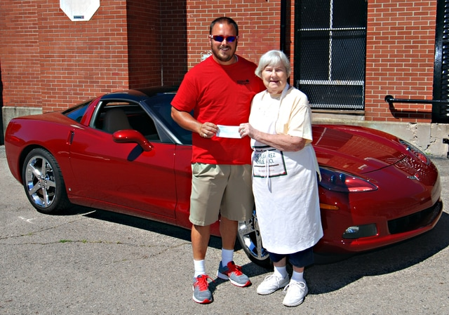 Mike Ullery | Daily Call Tom Lillicrap of the Miami Valley Corvette Club presents Wilma Earls of the Bethany Center with a donation check from proceeds of the clubs recent car show at Fountain Park, during a short ceremony at the Bethany Center on Wednesday.