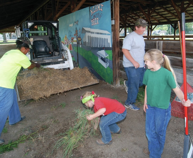 Mike Ullery | Daily Call Volunteers Demetria Woods, Candace Shellenbarger, 7, and Chloe Shellenbarger, 9, along with Junior Fair Board member Lane Davis, 15, spruce up the area around the Piqua Daily Call/Troy Daily News photo area at the Miami County Fairgrounds on Saturday as preparations for the 2015 Miami County Fair enter the home stretch. The fair begins next Friday.