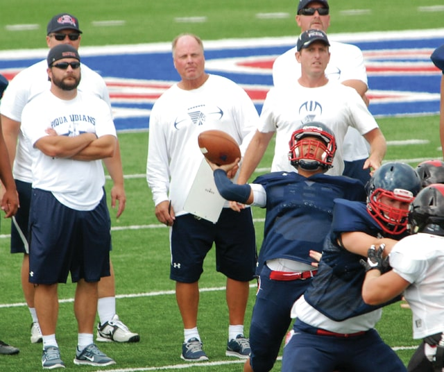 Mike Ullery | Daily Call Piqua football coaching staff members, including Eric Barge, Josh Smith, Rick Krejci, Troy Ouhl and Cledous Hawk, l-r, watch the Indians' offense, led by quarterback Rupert Delacruz, throwing pass, work against Tecumseh during a Tuesday scrimmage at Alexander Stadium/Purk Field. Tuesday was the first day the OHSAA allowed teams to scrimmage. Piqua opens regular season play on August 28 at Toledo St. Johns.