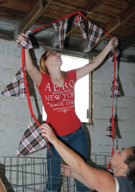 Mike Ullery | Daily Call Cheyenne Parke, 16, of Bradford hangs pennants above her goat pens at the Miami County Fairgrounds on Wednesday as her mom Shon, below right, and brother Simon, 12, out of frame, lend a helping hand.