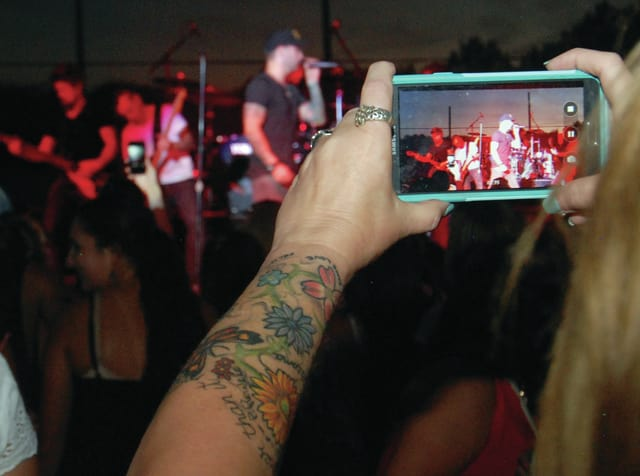 Mike Ullery | Daily Call A fan snaps a photo of featured artist Dallas Smith during Saturday's concert at the Miami County Fair.