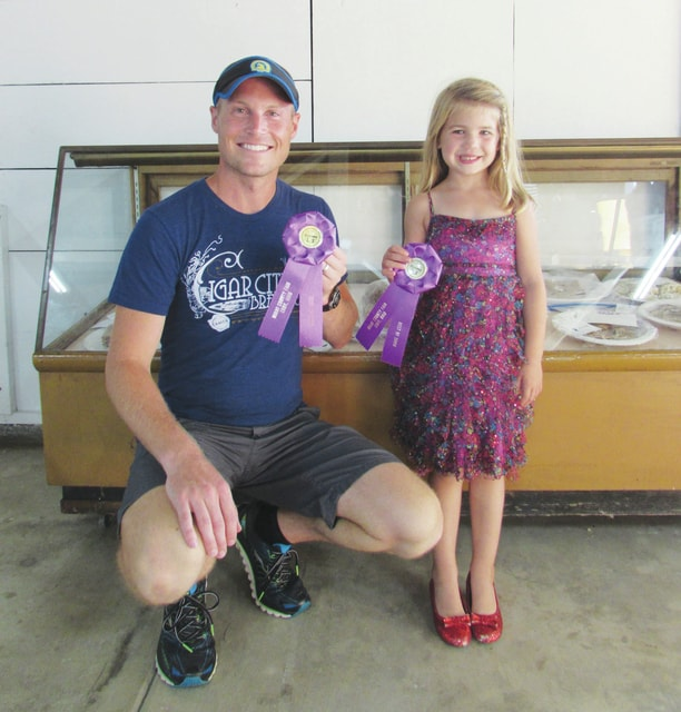 Kyle Brumbaugh (left) of Tipp City and his daughter Olivia, 5, (right) stand in front of their award-winning quick breads at the Miami County Fair Art Hall. Brumbaugh and his daughter each won a Best of Show award for their quick breads.