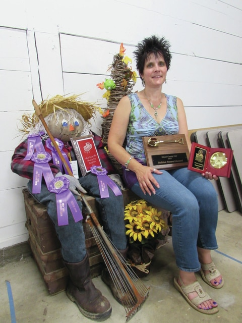 Terina Casanova of West Milton sits next to her scarecrow along with her numerous awards won at the Miami County Fair on Sunday. Casanova won the Homemaker of the Year award in addition to receiving the Golden Trowel award, the Miami County Fair Strawberry Day Best of Show award, five Best of Show awards, and approximately 56 ribbons overall.