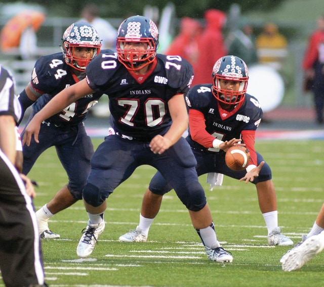 Mike Ullery/Daily Call Piqua quarterback Rupert Delacruz, 4, takes the snap from center Kyle Jones, 70, as Darien Tipps-Clemons, 44, readies to take the hand-off during Friday's game against Lima Senior at Alexander Stadium/Purk Field.