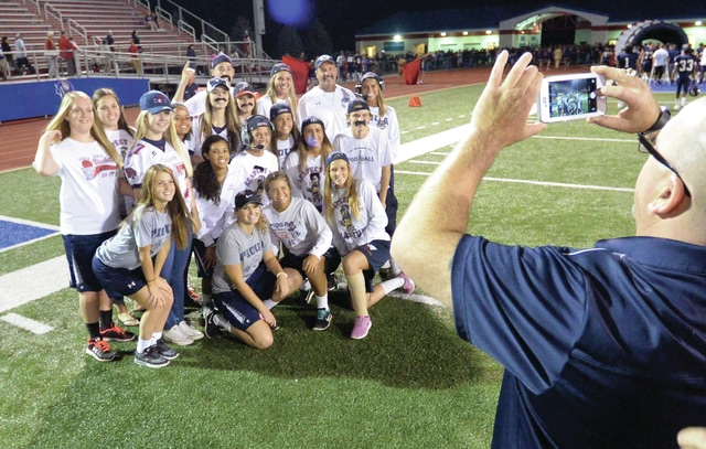 Mike Ullery/Daily Call Which one is Bill Nees? Piqua head football coach Bill Nees poses with members of the Indians student section who took part in Coach Nees Dress-Up night, following Friday's win over Fairborn.