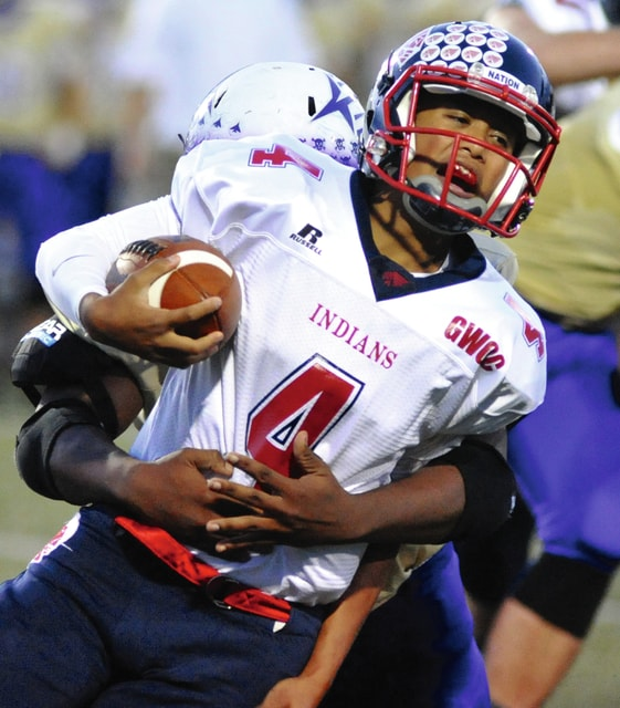 Mike Ullery/Daily Call Piqua quarterback Rupert Delacruz, 4, tries to elude a tackler against Vandalia-Butler last year.