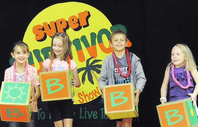 Anthony Weber | Civitas Media Hook Elementary School students including second grade students Sera Halter, Kenzy Copas and Aiden Kirkpatrick along with kindergarten student Gracelann Cales use blocks to answer questions reflecting the environment at a game of Super Survivor during an Illusion Maker presentation at the school Thursday in Troy.