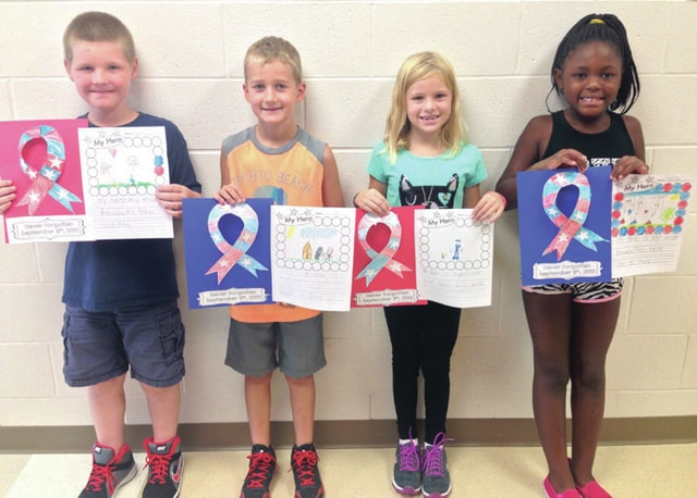 Springcreek Primary second grade students Kylan Hughes, Carter Davis, Kelsi Stahl, and Justice Carwley (left to right) show their projects illustrating who their heroes are in their lives as a result of learning about the Sept. 11 attacks on Friday.