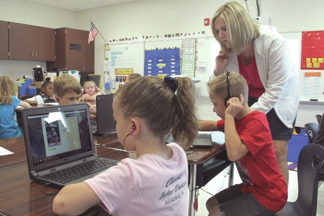 First grade students Presley Arzola, left, and Mason Casto, center, are working on their Raz-Kids reading program featured on the new Chromebooks at Piqua City Schools on Thursday. Jennifer Moore, right, assists Casto on his Chromebook.