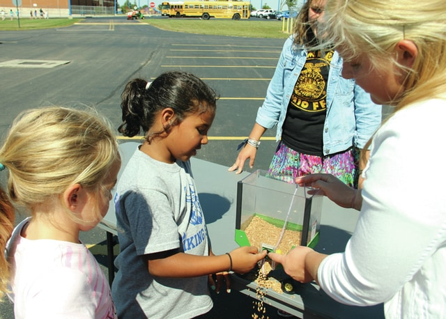 Second graders Kinsley Courtwright, left, and Whitney Enis, center, partake in the grain flow demonstration by FFA junior member Katie Bodenmiller on Thursday. The students learned that if caught in a grain wagon, as pictured, there is only five seconds for a person to escape or they will suffocate. This was all part of Farm Safety Week that was observed by Miami East Local Schools.