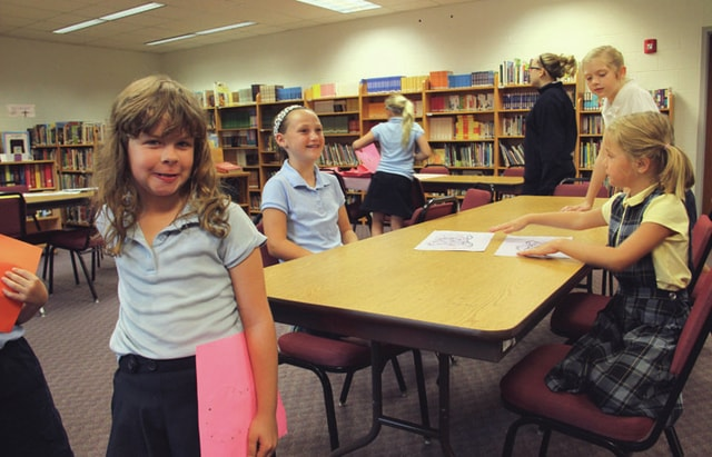 "Students at Piqua Catholic celebrated Spiritual Retreat Day on Friday, the day focusing on being servants of God. Pictured are Rebecca Henry, 8, left, Aubri Karn, 9, center, and Haylee Meckstroth, 5, right. The three were taking part in recreating the poem ""Foot Prints in Sand,"" by drawing designs on shoe illustrations."