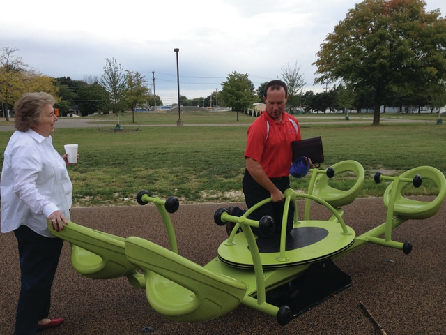 "Brian Brookhart, right, assistant director of the Piqua Public Works Department, demonstrates to Mayor Lucy Fess how kids can hang onto the center of the ""we-saw"" at the new, wheelchair-accessible playground located in Pitsenbarger Park."